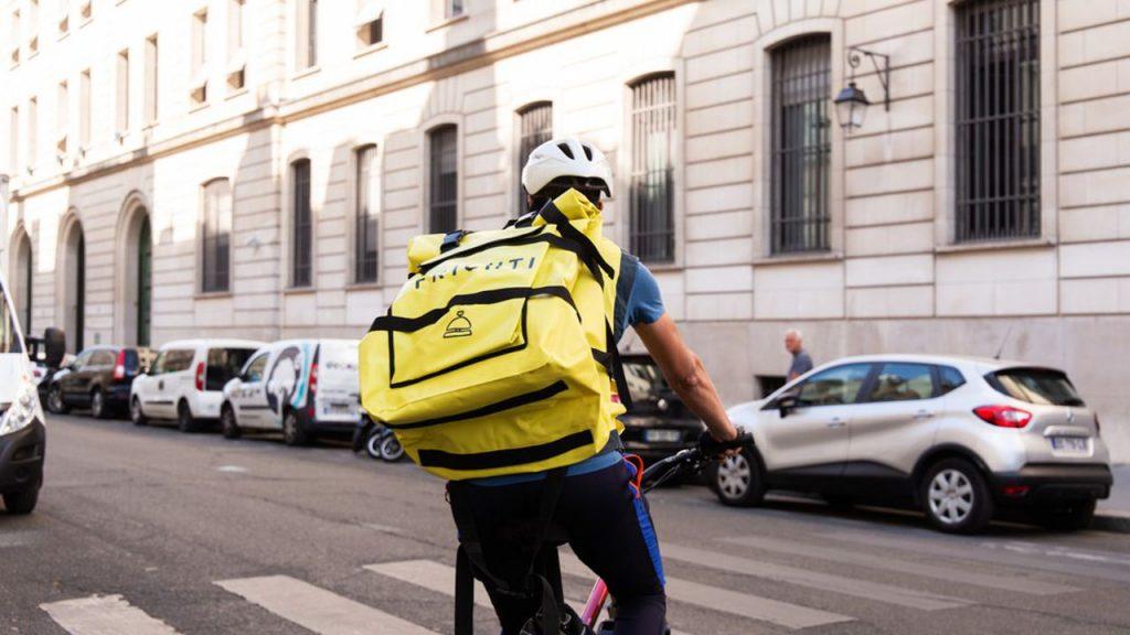 Il s'agit d'un homme à vélo qui effectue une livraison à domicile de nourriture. Il porte un sac à dos avec un logo.